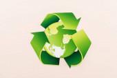 horní pohled na zelený recyklační symbol s planetou izolovanou na béžové