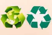 top view of green recycling symbols with planet isolated on beige