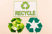 top view of green recycling symbols with planet and recycle word isolated on beige