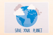 top view of placard with globe and save your planet lettering isolated on beige