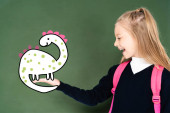 Photo schoolgirl pointing with hand at illustrated dinosaur on green chalkboard