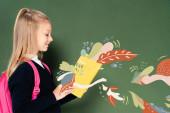 boční pohled školačky čtení knihy s víla ilustrace v blízkosti zelené tabuli