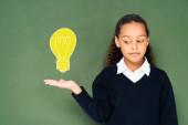 skeptická školačka ukazuje rukou na žárovku na zelené tabuli