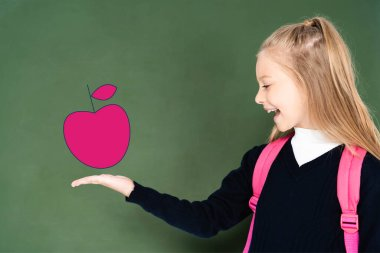 Schoolgirl pointing with hand at illustrated pink apple on green chalkboard stock vector