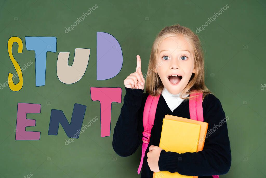 Excited schoolgirl holding book and showing idea gesture while standing near green chalkboard with student illustration stock vector