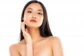junge Erwachsene asiatische Frau Blick auf Kamera und berühren Gesicht isoliert auf weiß