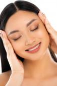 Portrét mladé asijské ženy se zavřenýma očima dotýkající se tváře izolované na bílém