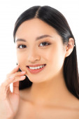 Photo Portrait of excited young asian woman looking at camera and touching face isolated on white
