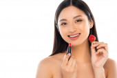 naked asian woman looking at camera while holding sweet strawberry and red lipstick near face isolated on white
