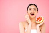 vzrušená asijská žena drží polovinu šťavnaté grapefruit a zároveň dotýká tvář izolované na růžové