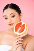 Asijská žena drží polovinu zralého grapefruitu v blízkosti obličeje izolované na růžové