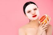 brunetky asijské žena v obličeji maska drží polovinu zralého grapefruitu při pohledu na kameru izolované na růžové