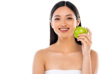 Excited young asian woman looking at camera and holding apple isolated on white stock vector
