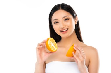 Brunette asian woman looking at camera while holding halves of juicy orange isolated on white stock vector