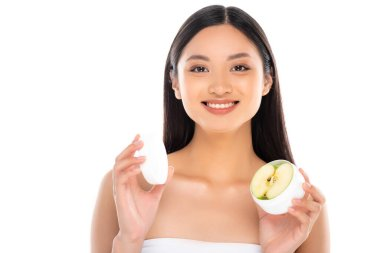 Brunette asian woman holding container of cosmetic cream with half of apple isolated on white stock vector