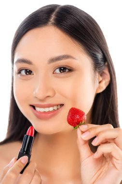 Young asian woman looking at camera while holding red lipstick and fresh strawberry near face isolated on white stock vector