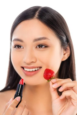 Brunette asian woman looking away while holding red lipstick and ripe strawberry near face isolated on white stock vector