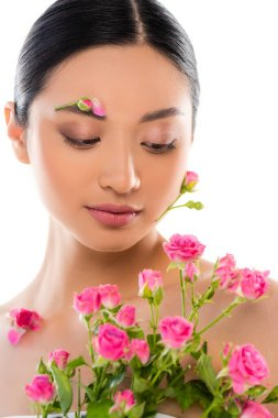 Naked asian woman with floral decoration on face near pink roses isolated on white stock vector