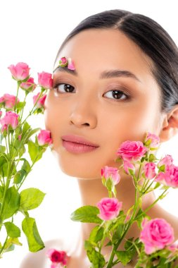 Portrait of young asian woman with floral decor on face near pink roses isolated on white stock vector