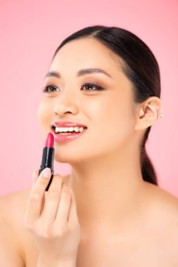 Nude asian woman looking away while applying lipstick isolated on pink stock vector
