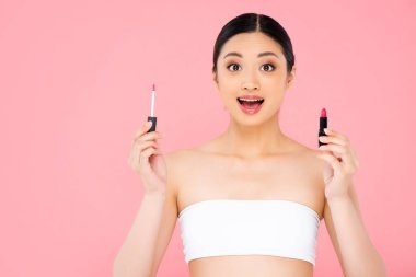 Excited asian woman looking at camera while holding lip gloss and lipstick isolated on pink stock vector