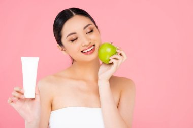 Asian woman with closed eyes holding cosmetic cream and green apple isolated on pink stock vector