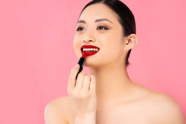 Naked asian woman looking away while applying red lipstick isolated on pink stock vector