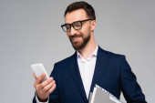 young businessman in blue blazer and eyeglasses looking at mobile phone isolated on grey
