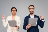 vzrušený pár mezirasových obchodních kolegů ukazující myšlenkové gesto při držení složek izolovaných na šedé