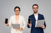 couple of interracial business colleagues holding folders and smartphones with blank screen isolated on grey