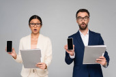 shocked interracial business partners holding folders while showing mobile phones with blank screen isolated on grey
