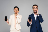 surprised interracial couple of business colleagues touching faces while holding smartphones with blank screen isolated on grey