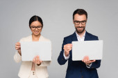 interracial couple of business colleagues in eyeglasses holding laptops isolated on grey
