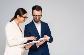 interracial couple of business colleagues in blazers and eyeglasses using digital tablets isolated on grey