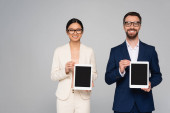 interracial couple of business partners in eyeglasses showing digital tablets with blank screen isolated on grey