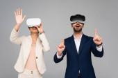 vzrušení obchodní partneři ve virtuálních sluchátkách gestikulují, jako by se dotýkali něčeho izolovaného na šedi