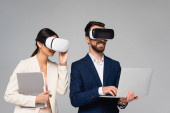 businesswoman touching vr headset near businessman using laptop isolated on grey