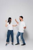 junges gemischtrassiges Paar in Jeans, weißen T-Shirts und Gummischuhen, die tanzen, während sie einander auf weiß anschauen