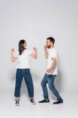 plný pohled na vzrušený mezirasový pár v džínách, bílých tričkách a gumových obuvích tančících na bílém