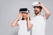 vzrušený mezirasový pár v bílých tričkách dotýkající se vr sluchátek při pohledu pryč s otevřenými ústy na šedé