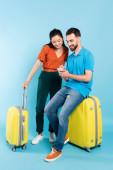 mladý muž v polo t-shirt pomocí smartphone zatímco sedí na kufru v blízkosti asijské ženy v červené blůze na modré