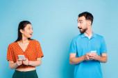vzrušený mezirasový pár dívá na sebe při držení smartphony na modré