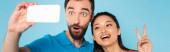 panoramatický koncept asijské ženy ukazující mír gesto v blízkosti přítele šklebící se při braní selfie izolované na modré