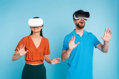 excited man in polo t-shirt and woman in red blouse using vr headsets while gesturing with hands on blue