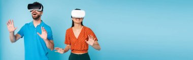 panoramic concept of excited man in polo t-shirt and woman in red blouse gesturing with hands while using vr headsets on blue