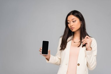 Thoughtful asian businesswoman in blazer holding eyeglasses while showing smartphone with blank screen isolated on grey stock vector