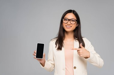 Young asian businesswoman in eyeglasses pointing with finger at smartphone with blank screen isolated on grey stock vector