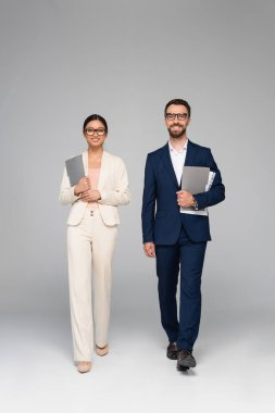 Interracial couple of business colleagues looking at camera while walking with folders on grey stock vector