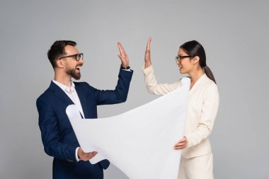 Interracial couple of business colleagues holding white placard and giving high five isolated on grey stock vector