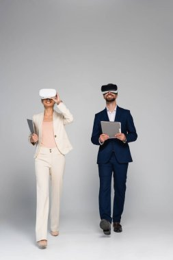 Full length view of business partners in vr headsets holding folders while walking on grey stock vector